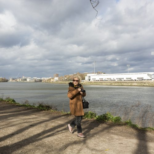 2017-02-23-Wandsworth_Thames-Path-towards-Putney_Landscape_People-Gordana-in-front-of-Fulham-Football-Ground-unphases-by-the-wind